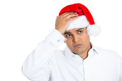 A young man wearing xmas hat expressing grief Royalty Free Stock Image