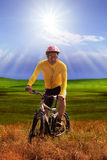 Young man wearing yellow bicycle shirt  riding mountain bike mtb. In grass field against sun shining on blue sky use for out door and extreme sport leisure Royalty Free Stock Photo
