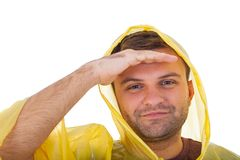 Young man wearing a yellow raincoat. Picture of a caucasian young man wearing a yellow raincoat, posing on isolated background stock photography