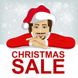 Young man wearnig santa hat leaned on blank board with red christmas sale text Stock Photos