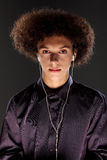 Young man wears music ear plugs and big afro hair Stock Images