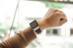 Young man wears smart watch working on table.  Stock Images