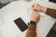 Young man wears smart watch working on table Stock Photos