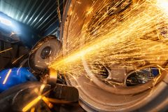 A close-up of a car mechanic. A young man welder in a blue gloves grinder bearing metal an angle grinder in the workshop, sparks fly to the side stock photos