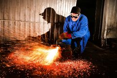 The young man, a welder cut off a piece of metal autogenous welding. royalty free stock photo