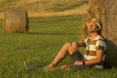 Young man in wheat field leaning on haystack Stock Photos