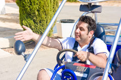 Young man at wheel of buggy shows hand aside royalty free stock photo