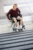 Young man in wheel chair in front of stairs looking sad Royalty Free Stock Images