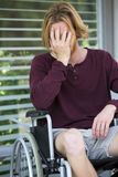 Young man in wheel chair looking desperate Stock Photo