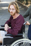 Young man in wheel chair looking sad Royalty Free Stock Image