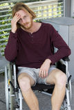 Young man in wheel chair looking sad Stock Photography