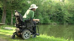 4k resolution of happy man in a electric wheelchair fishing at the beautiful pond in natue on a sunny day