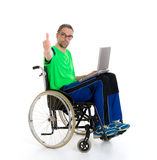 Young man in a wheelchair with laptopand thumb up Royalty Free Stock Photos