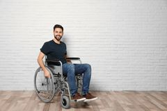 Young man in wheelchair near brick wall indoors. Space for text royalty free stock images