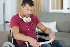 Young man on wheelchair reading book at home Royalty Free Stock Photography