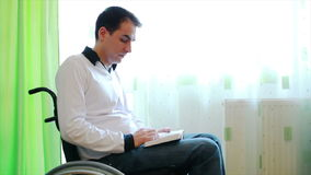 Young man in wheelchair reading a book Royalty Free Stock Photo