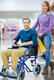 Young Man in Wheelchair Shopping with Wife Stock Image