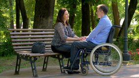 Young man on wheelchair talking with his wife in park stock video