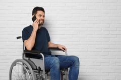 Young man in wheelchair talking on phone near brick wall indoors. Space for text stock images