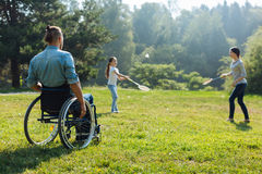 Young man in wheelchair watching his family play badminton. Enjoying sports. Pleasant young men with mobility impairment sitting in the wheelchair and watching Stock Images