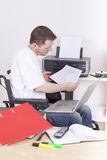 Young man on wheelchair at work Royalty Free Stock Photography