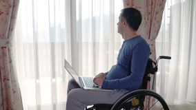 Young man in wheelchair working at laptop computer at home stock footage