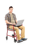 Young man in wheelchair working on a laptop Stock Images