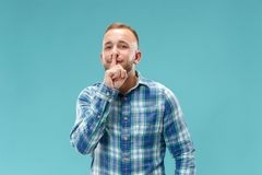 The young man whispering a secret behind her hand over blue background. Secret, gossip concept. Young man whispering a secret behind his hand. Businessman stock images