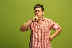 The young man whispering a secret behind her hand over green background. Secret, gossip concept. Young man whispering a secret behind his hand. Businessman stock photo