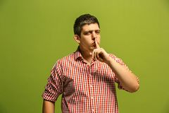 The young man whispering a secret behind her hand over green background. Secret, gossip concept. Young man whispering a secret behind his hand. Businessman stock images