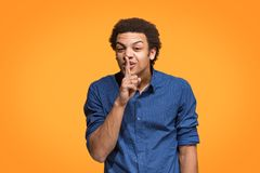 The young man whispering a secret behind her hand over orange background. Secret, gossip concept. Young man whispering a secret behind his hand. Businessman stock image