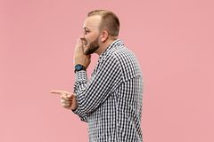 The young man whispering a secret behind her hand over pink background. Secret, gossip concept. Young man whispering a secret behind his hand. Businessman royalty free stock image