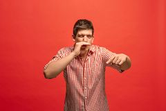 The young man whispering a secret behind her hand over red background. Secret, gossip concept. Young man whispering a secret behind his hand. Businessman stock photos
