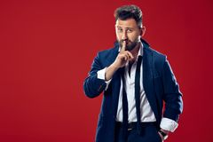 The young man whispering a secret behind her hand over red background. Secret, gossip concept. Young man whispering a secret behind his hand. Businessman royalty free stock photo