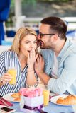 Young man whispering a secret to his girlfriend stock photos