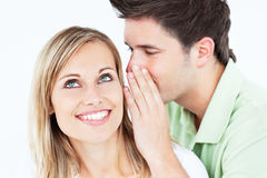 Young man whispering something to his girldfriend stock photos