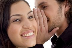 Young man whispering to woman Royalty Free Stock Images