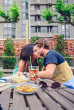 Young man whispering to woman sitting outdoors. Young men whispering to beautiful women sitting around of table with healthy drinks and snacks in a summer day Royalty Free Stock Photos