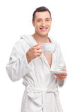 Young man in a white bathrobe holding a cup of tea Royalty Free Stock Photos
