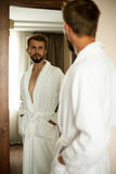 Young man in bathrobe stands in front of mirror and looks at his royalty free stock image