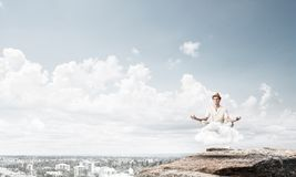 Young man keeping mind conscious. Young man in white clothing keeping eyes closed and looking concentrated while meditating on cloud in the air with city view Royalty Free Stock Image