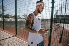 Young man with white headband on his head and tattoos on his arms dressed in the white t-shirt stands next to the royalty free stock images