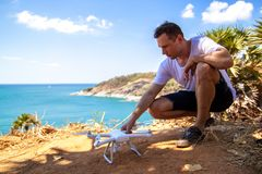 Man in a shirt operating a drone with remote control on the sea. stock photography
