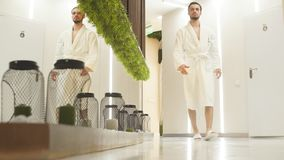 Young man in white robe walks down the hall of luxurious Spa center talking on mobile phone. stock video