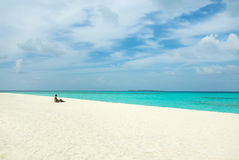 Young man on white sand beach on Maldives Stock Photo