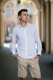 A young man in a white shirt beige breeches holds his hands in pockets on a colorful blurred background. royalty free stock images
