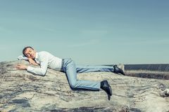 A young man in a white shirt and blue trousers is lying royalty free stock photos