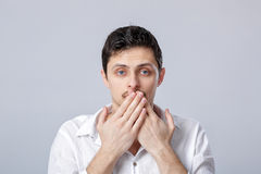 Young man in white shirt covers his mouth with his hands on gray Stock Photo
