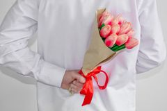 A young man in a white shirt, holding a bouquet of tulips, in his hand behind his back, on a white background. Valentine`s Day stock images