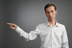 Young man in white shirt is pointing at something, standing on grey background. Stock Photography